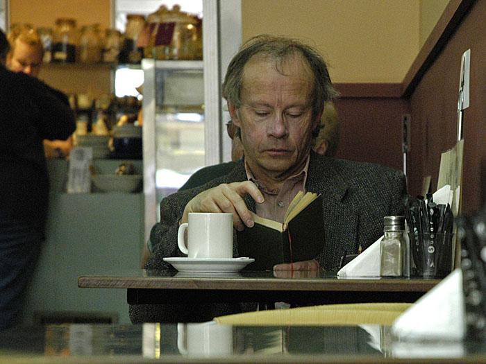 Gentleman seated in cafe, reading a book
