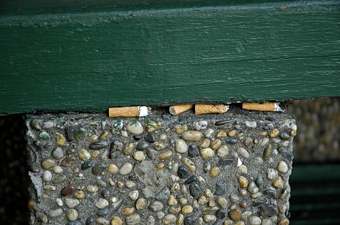 Cigarette butts jammed in public bench