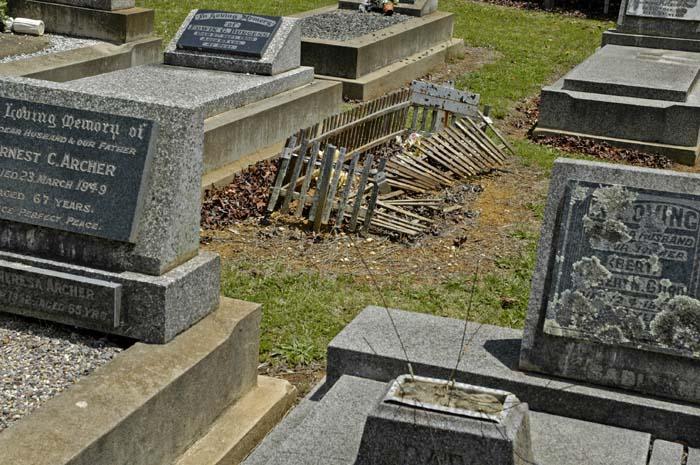 Timber grave border amongst granite