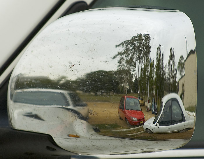 Parked cars reflected in a car wing mirror